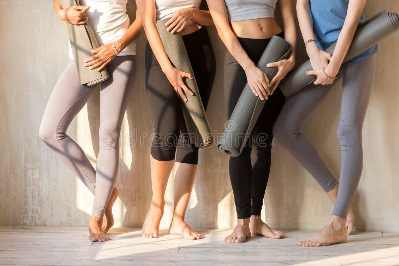 Grupp av sportive flickor i rad med yogamats royaltyfri foto