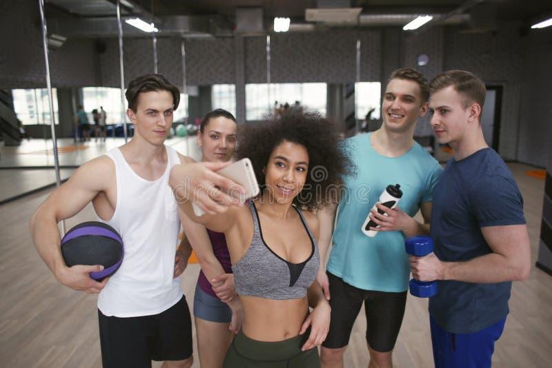 Grupp av sportive folk som tar selfie i idrottshall arkivfoto
