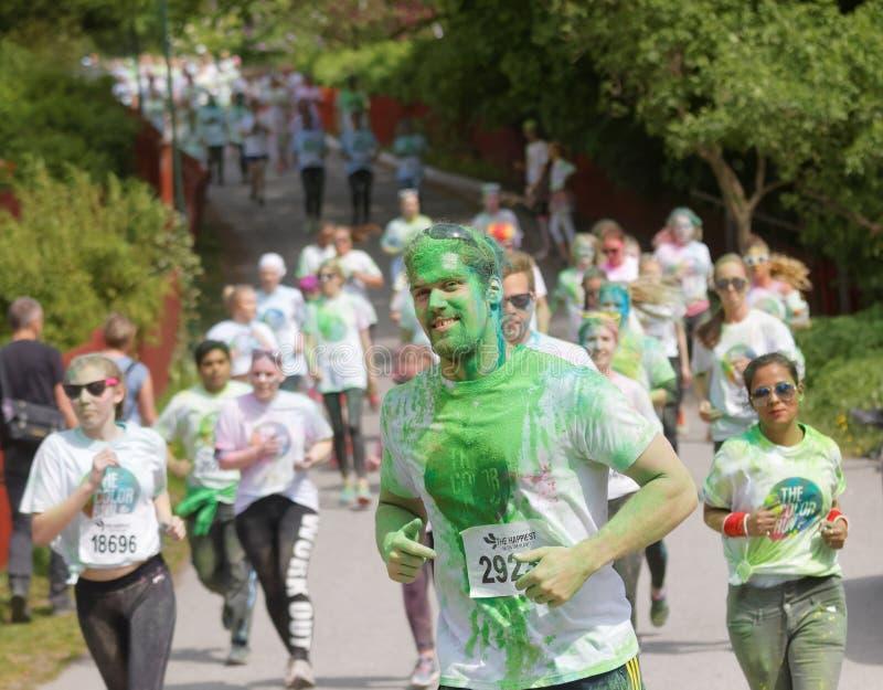 Grupp av spring, lyckligt som ler tonåringar som täckas med färgrikt arkivbilder
