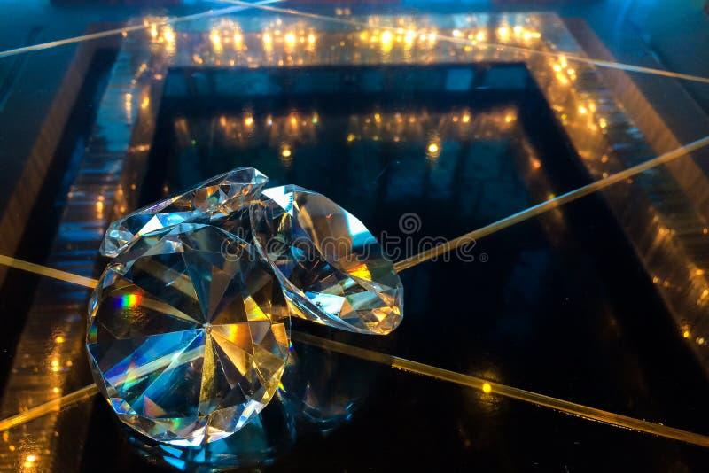 Grupp av stora diamanter som skiner på den Glass tabellen för reflexionssvart på hörnet som används som mall royaltyfri fotografi