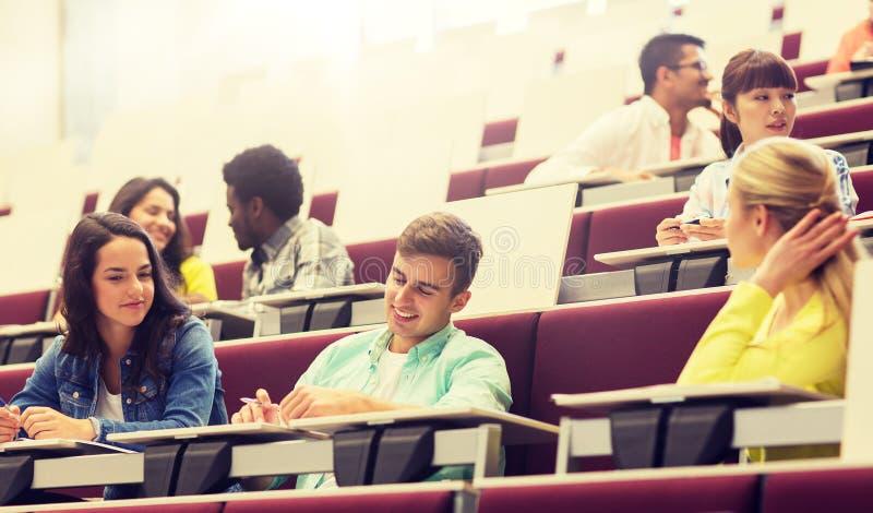 Grupp av studenter med anteckningsb?cker i h?rsal royaltyfri fotografi