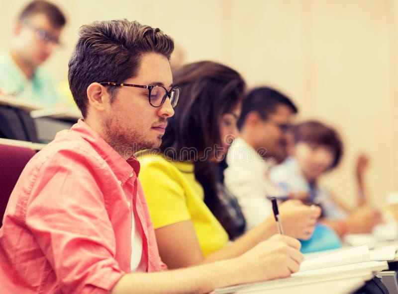 Grupp av studenter med anteckningsb?cker i h?rsal royaltyfri bild