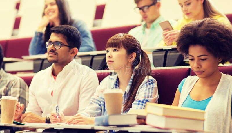 Grupp av studenter med anteckningsb?cker p? f?rel?sning royaltyfria bilder