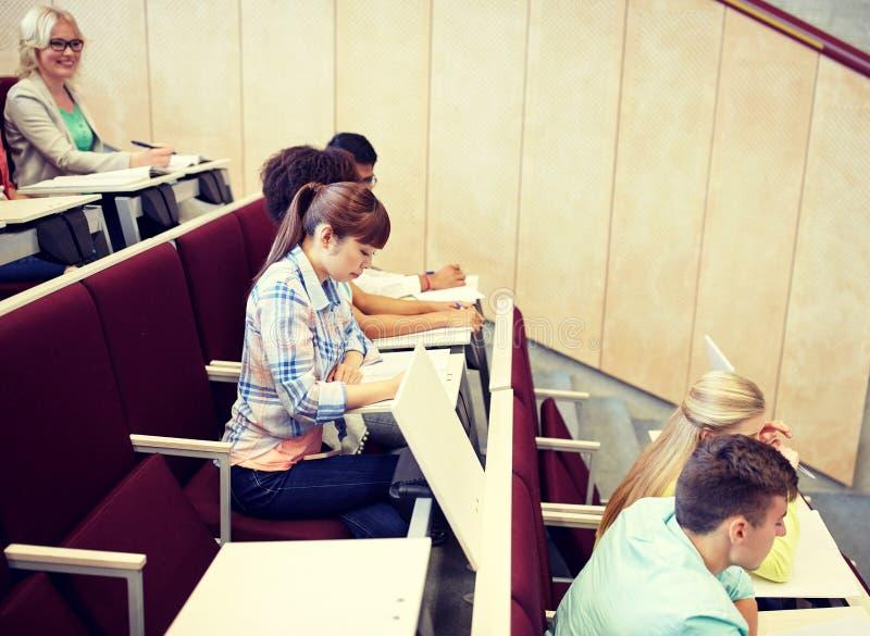 Grupp av studenter med anteckningsb?cker p? h?rsalen arkivfoton
