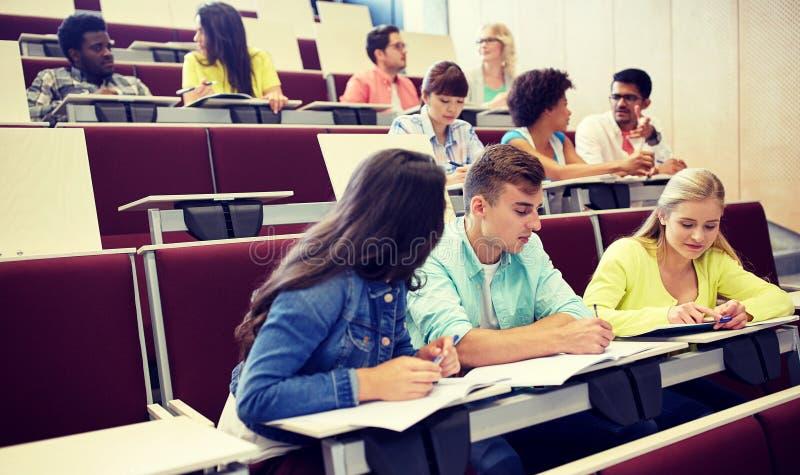 Grupp av studenter med anteckningsb?cker p? h?rsalen royaltyfri fotografi
