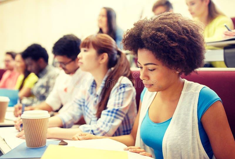 Grupp av studenter med kaffehandstil p? f?rel?sning royaltyfria foton