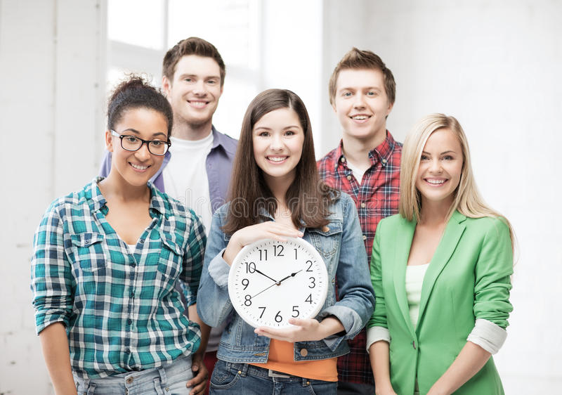 Grupp av studenter på skolan med klockan royaltyfri bild
