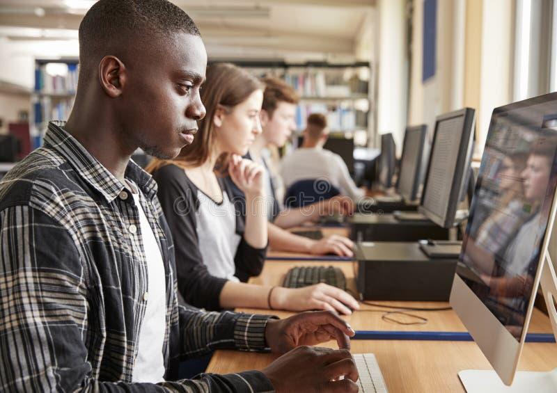 Grupp av studenter som använder datorer i högskolaarkiv royaltyfria foton