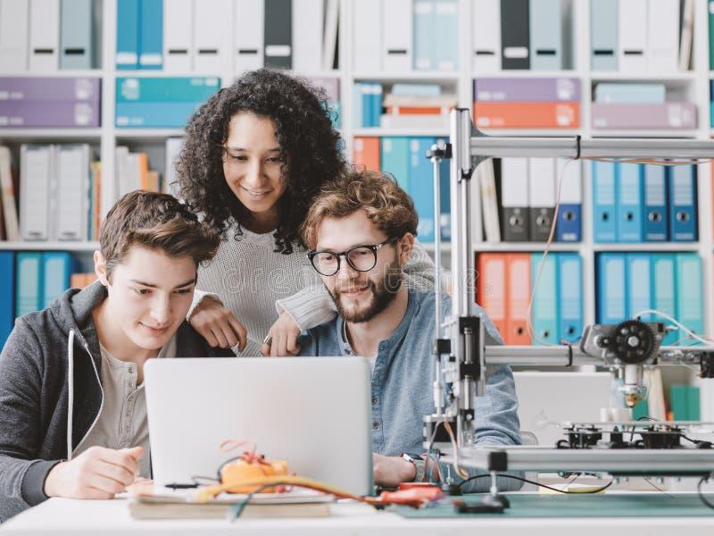 Grupp av studenter som använder en skrivare 3D och en bärbar dator royaltyfri bild