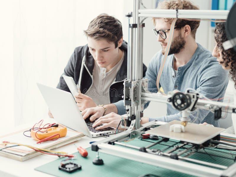 Grupp av studenter som använder en skrivare 3D och en bärbar dator royaltyfria foton