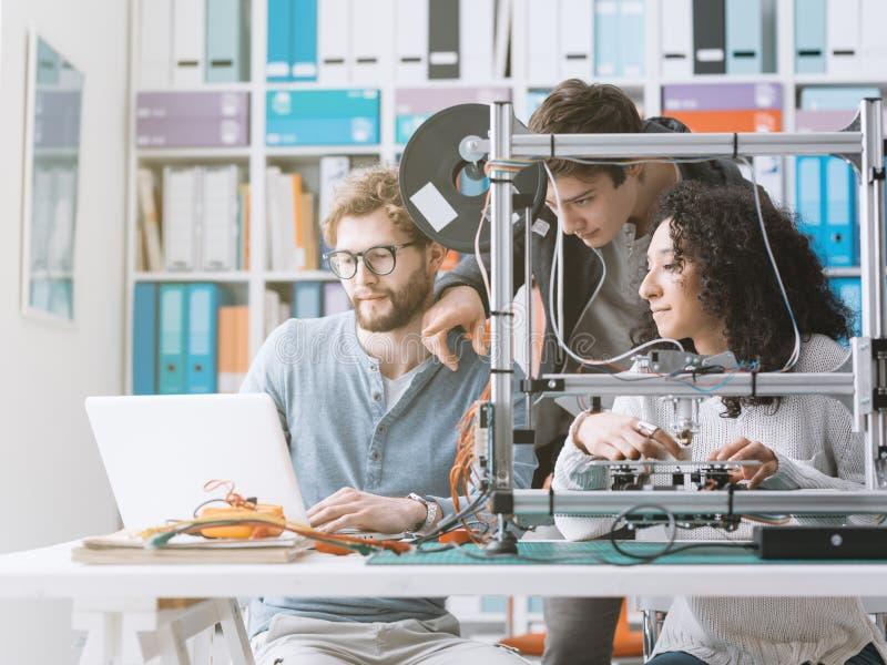 Grupp av studenter som använder en skrivare 3D och en bärbar dator fotografering för bildbyråer