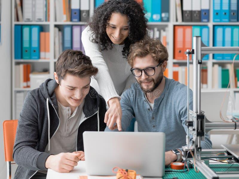 Grupp av studenter som använder en skrivare 3D och en bärbar dator arkivbild