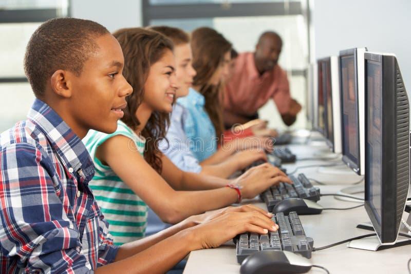 Grupp av studenter som arbetar på datorer i klassrum royaltyfri fotografi