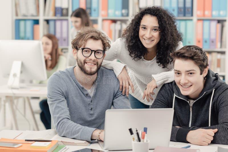 Grupp av studenter som förbinder med en bärbar dator royaltyfri fotografi