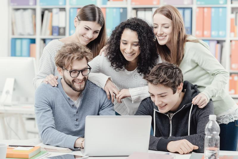 Grupp av studenter som förbinder med en bärbar dator royaltyfri foto