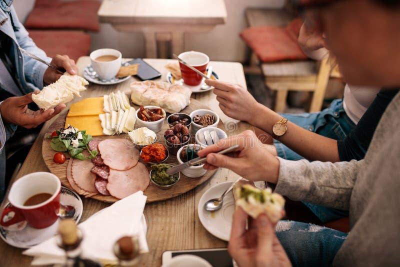 Grupp av studenter som har mat i högskolakantin royaltyfria bilder
