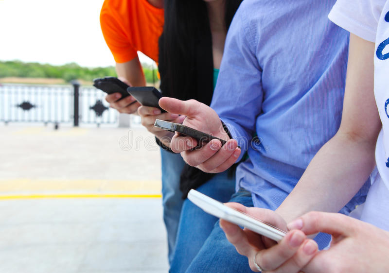 Grupp av studenter som pratar med deras smartphones royaltyfria foton