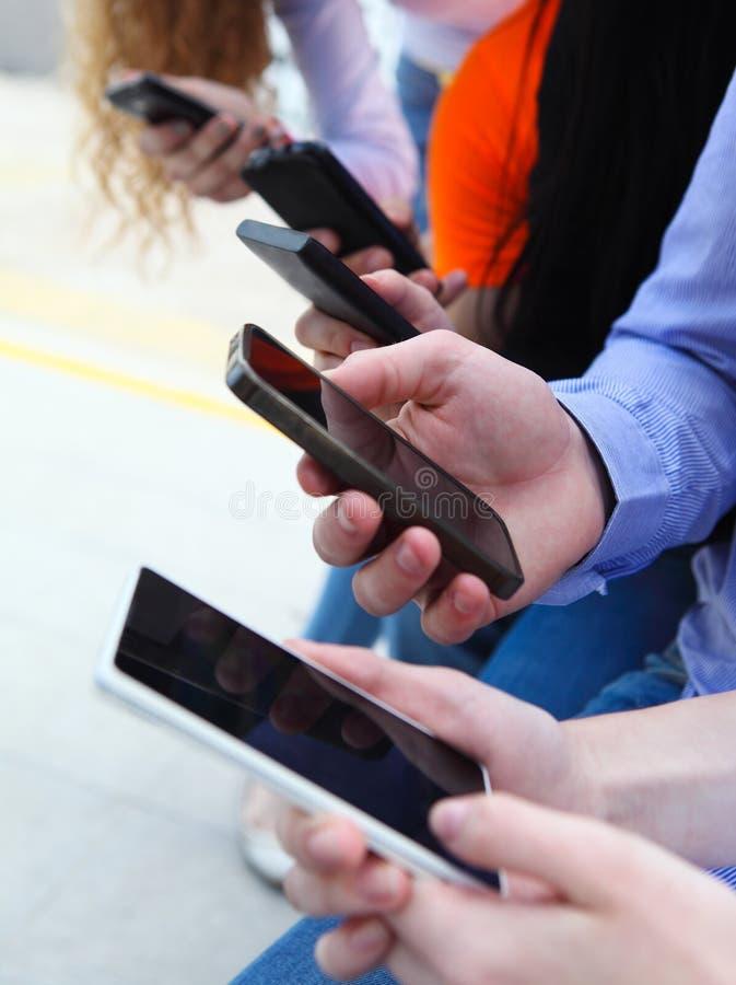 Grupp av studenter som pratar med deras smartphones royaltyfria bilder
