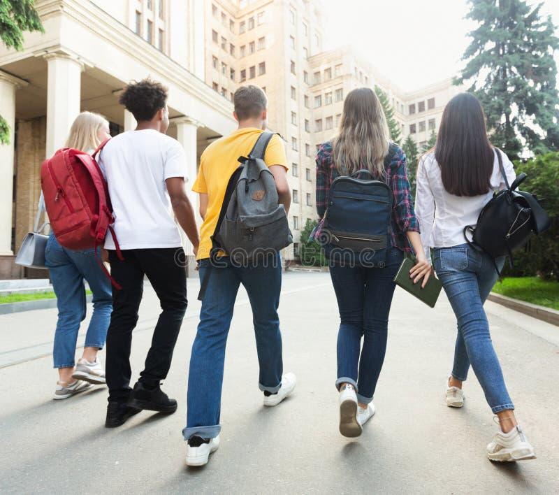 Grupp av studenter som tillsammans går i universitetsområde efter studier arkivbilder