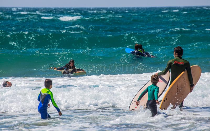 Grupp av surfare på den Cascais stranden på en solig dag, Portugal royaltyfri fotografi