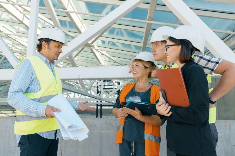 Grupp av teknikerer, byggmästare, arkitekter på byggnadsplatsen Konstruktions-, utvecklings-, teamwork- och folkbegrepp arkivbilder