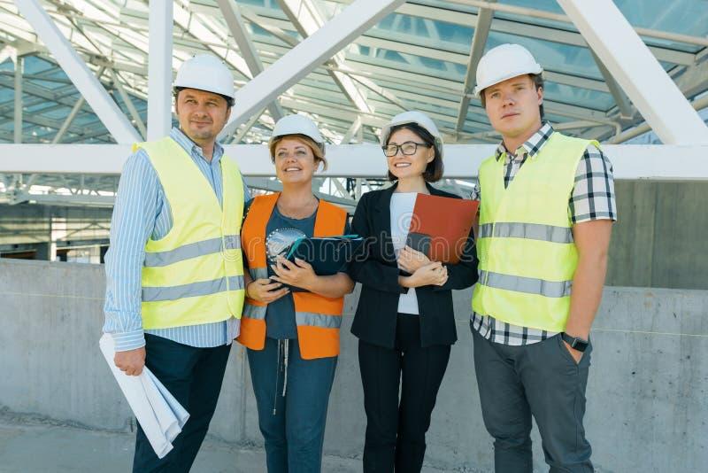 Grupp av teknikerer, byggmästare, arkitekter på byggnadsplatsen Konstruktions-, utvecklings-, teamwork- och folkbegrepp royaltyfri bild