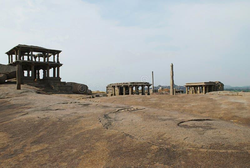 Grupp av tempel, Hemakuta kulle, Hampi, Karnataka Sakral mitt Storeyed nyckel två på de vänstra och högväxta monolitiska lampstol arkivfoto