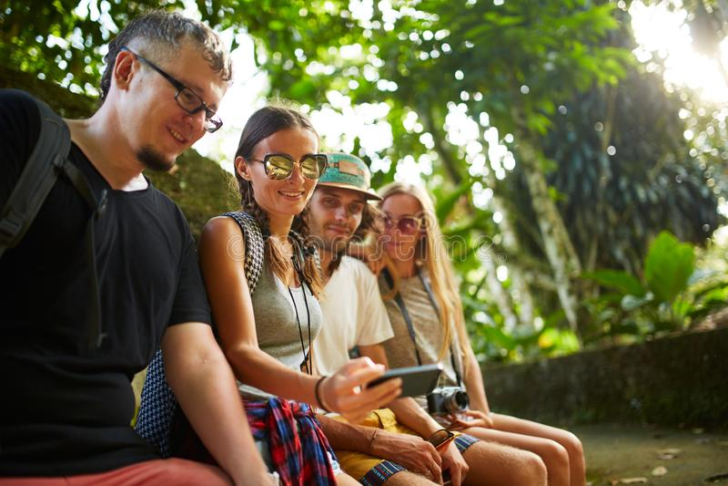 Grupp av tillbaka packande turister som ser smartphonen i thai djungel royaltyfria bilder