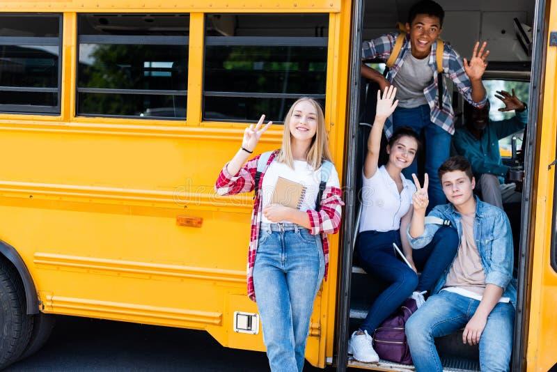 grupp av tonåriga forskare som sitter på skolbussen med chaufförinsidan och visar olika gester royaltyfri foto