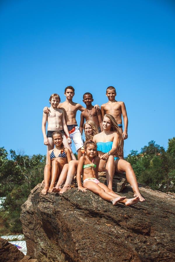 Grupp av tonåriga vänner på stranden royaltyfri fotografi
