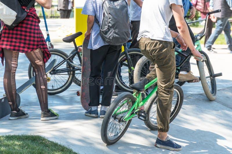 Grupp av tonåringar med cyklar i parkera fotografering för bildbyråer