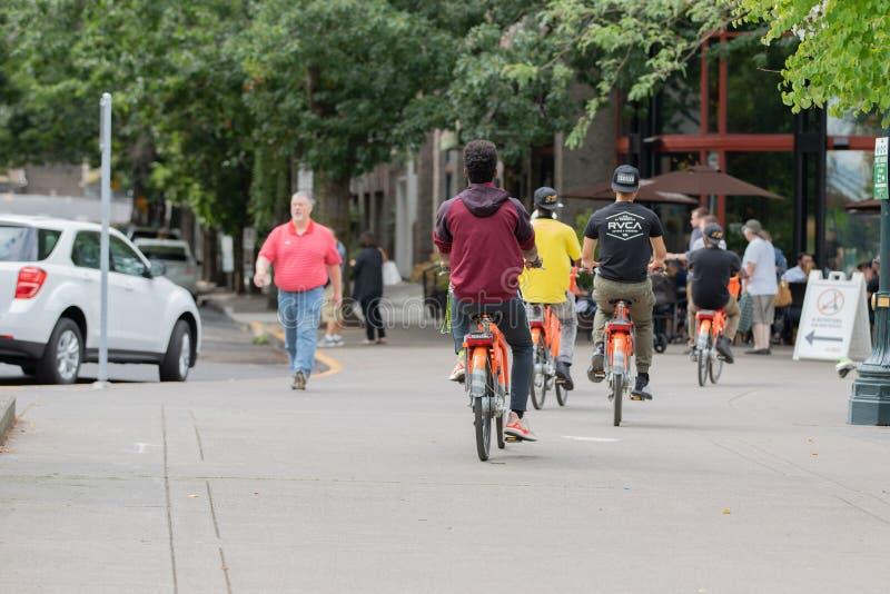 Grupp av tonåringar på uthyrnings- cyklar arkivfoton