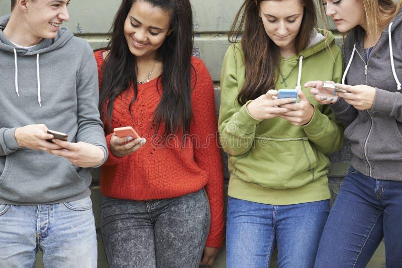 Grupp av tonåringar som delar textmeddelandet på mobiltelefoner royaltyfria foton