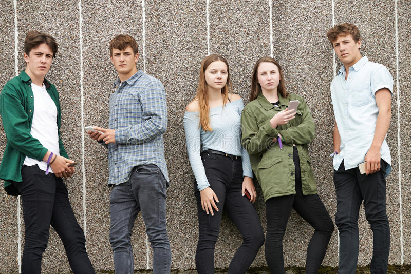 Grupp av tonåringar som delar textmeddelandet på mobiltelefoner arkivbilder
