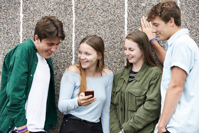 Grupp av tonåringar som ser textmeddelandet på mobiltelefonen arkivbilder