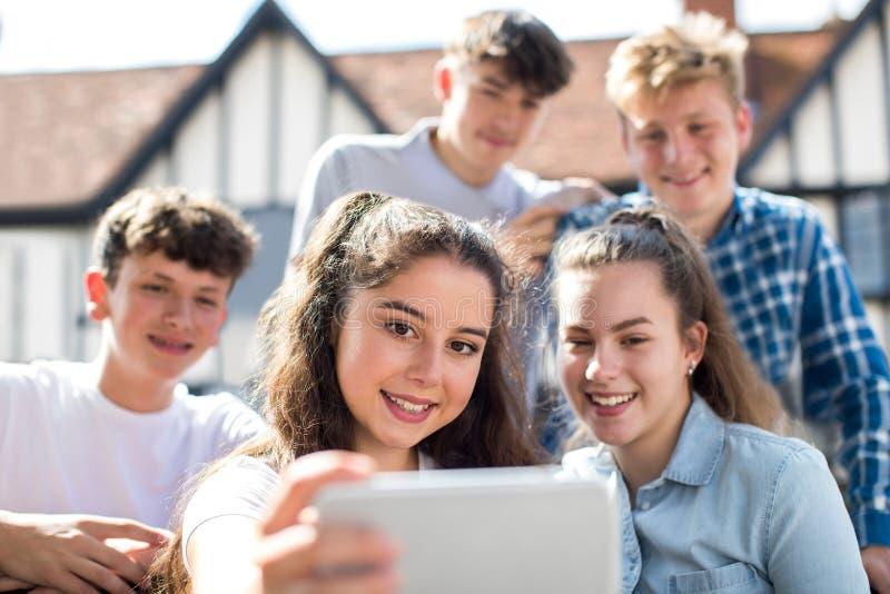 Grupp av tonåringar som utomhus tar Selfie på mobiltelefonen arkivfoton