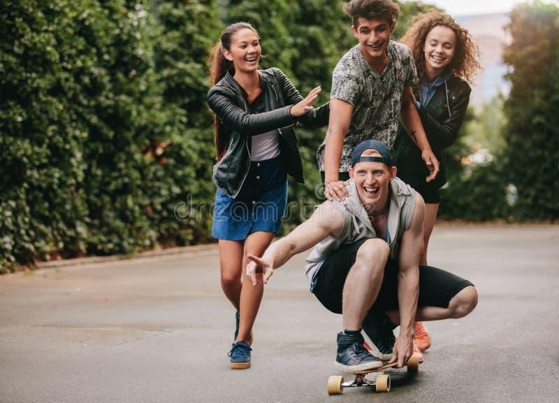 Grupp av tonåringar som utomhus tycker om med skateboarden arkivbilder