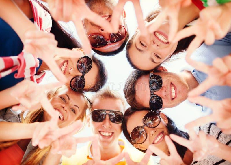 Grupp av tonåringar som visar gest för finger fem fotografering för bildbyråer