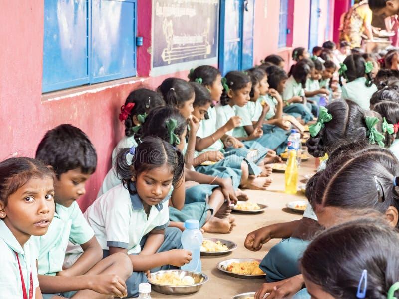 Grupp av tonåringelever som tjänas som målplattan av ris i regeringskolakantin Sjuklig mat för fattiga barn royaltyfri foto