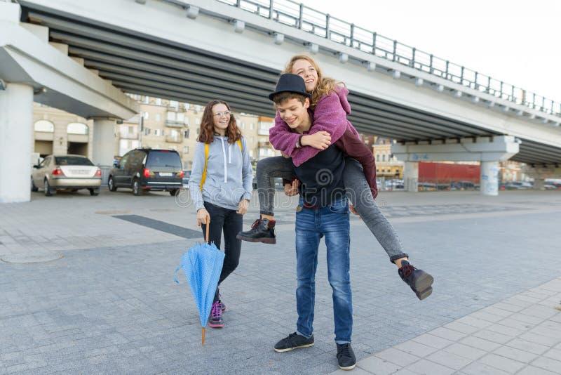 Grupp av tonåringvänner som har gyckel i staden som skrattar ungar med paraplyet Stads- tonårig livsstil arkivbilder