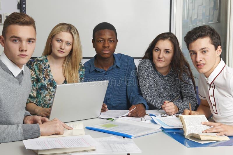 Grupp av tonårs- elever som arbetar i klassrum royaltyfria foton