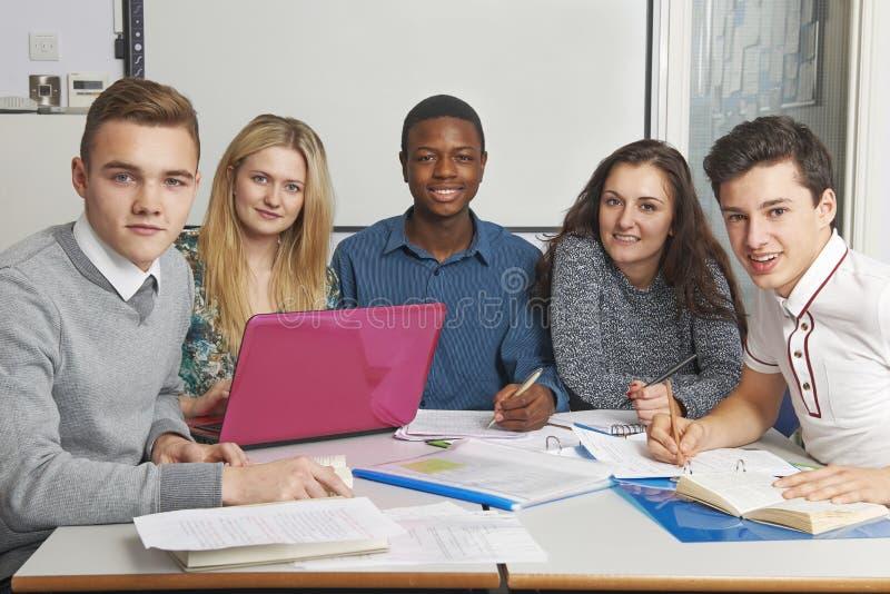 Grupp av tonårs- elever som tillsammans arbetar i klassrum arkivfoto