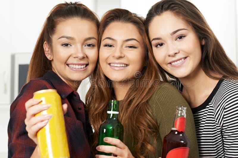 Grupp av tonårs- flickor som dricker alkohol på partiet arkivbilder