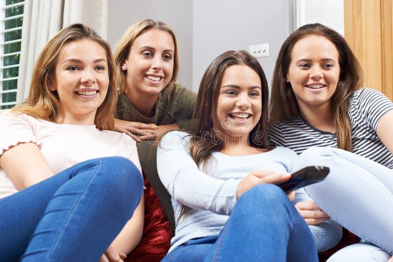 Grupp av tonårs- flickor som hemma håller ögonen på TV tillsammans arkivbild