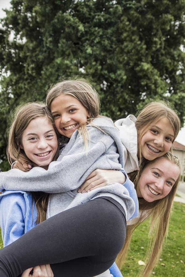 Grupp av tonårs- flickor som tillsammans spelar och utomhus ler arkivfoton