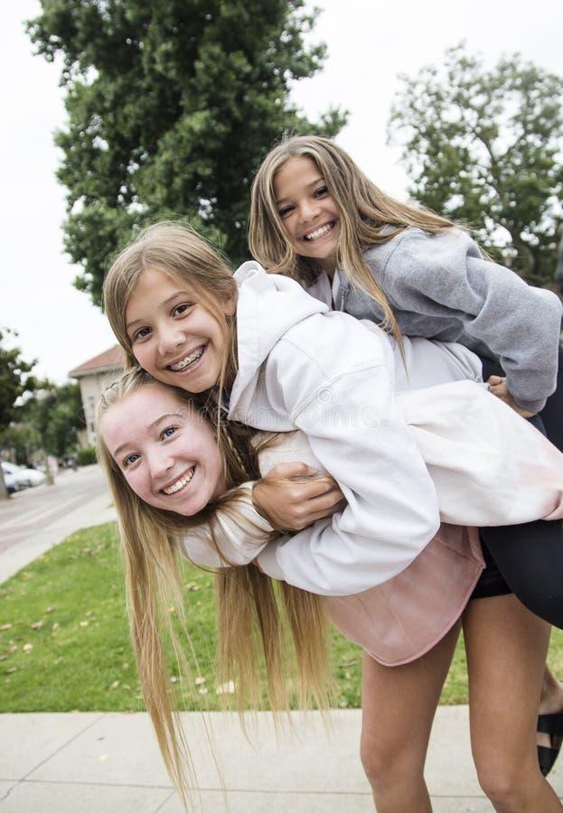 Grupp av tonårs- flickor som tillsammans spelar och utomhus ler arkivbild