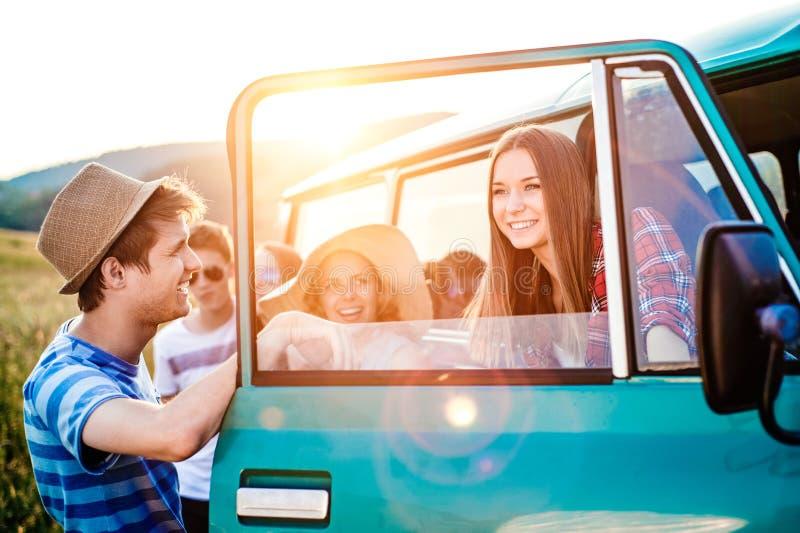 Grupp av tonårs- hipsters på en roadtrip som är campervan royaltyfri fotografi