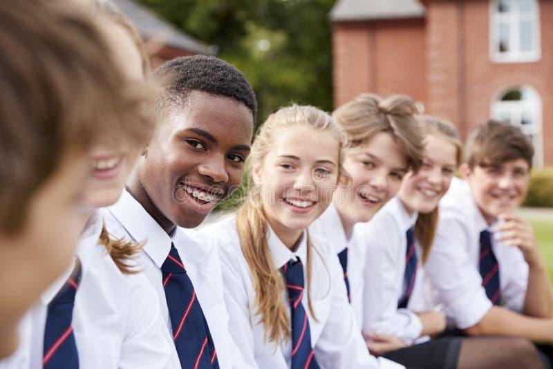 Grupp av tonårs- studenter i enhetliga utvändiga skolabyggnader arkivbild