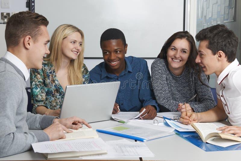 Grupp av tonårs- studenter som arbetar i klassrum royaltyfri bild