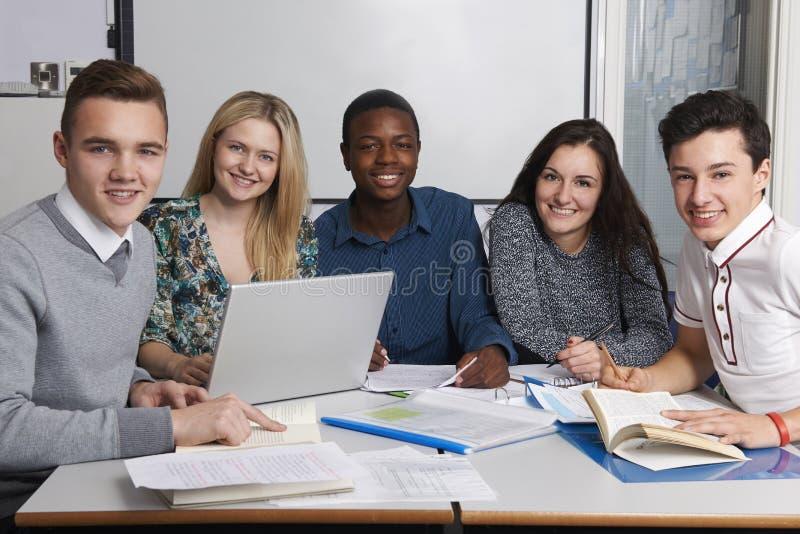 Grupp av tonårs- studenter som arbetar i klassrum arkivbild